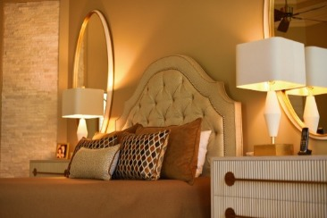 bedroom with tufted headboard and oval mirror
